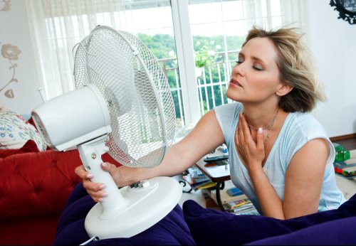 woman trying to cool down at home with a fan - there are better solutions to keep you cool at home without breaking the bank.