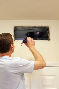 man cleaning his air conditioning system